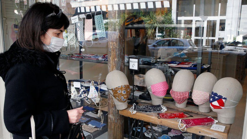 A woman wearing a face mask looks at face masks on sale in Paris
