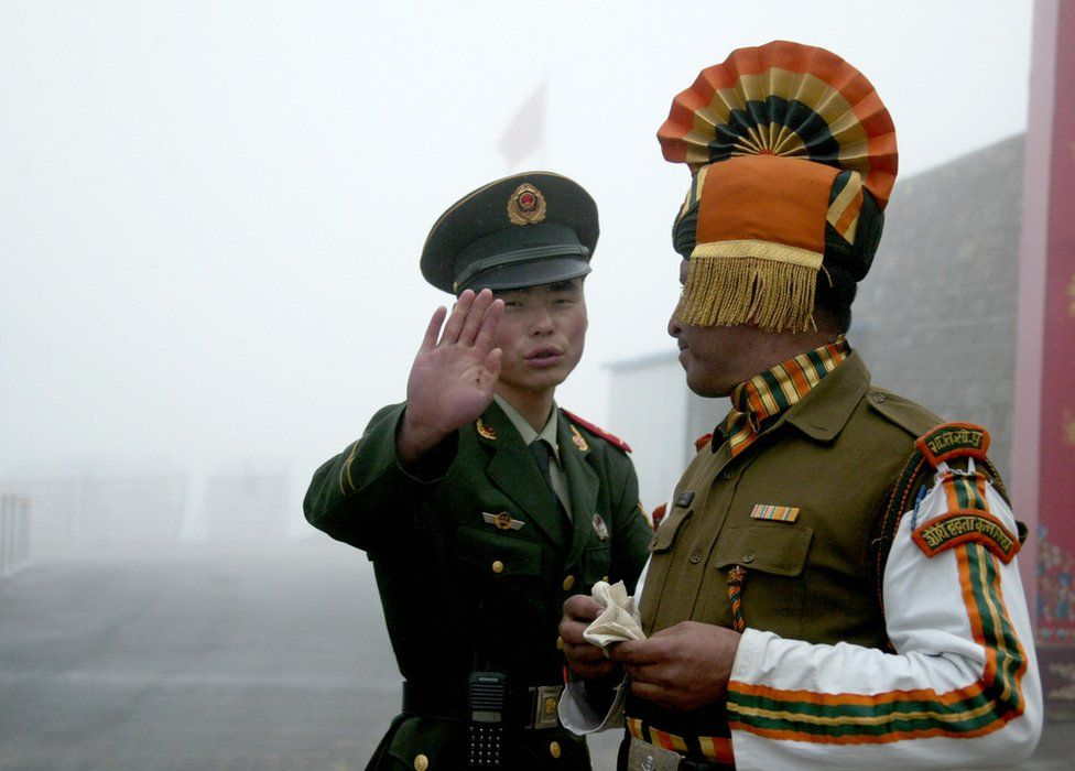 In this photograph taken on July 10, 2008, A Chinese soldier gestures as he stands near an Indian soldier on the Chinese side of the ancient Nathu La border crossing between India and China