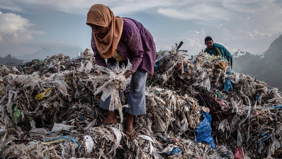 A woman collecting plastic to recycle at a import plastic waste dump in Indonesia.
