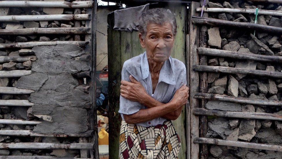 A shivering woman stands outside her damaged home