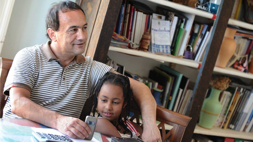 Domenico Lucano with Ethiopian child in Riace in 2011