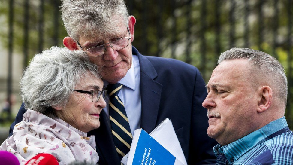 Kate McCausland is embraced by Jon McCourt and accompanied by John Heaney outside Belfast's Laganside Courts