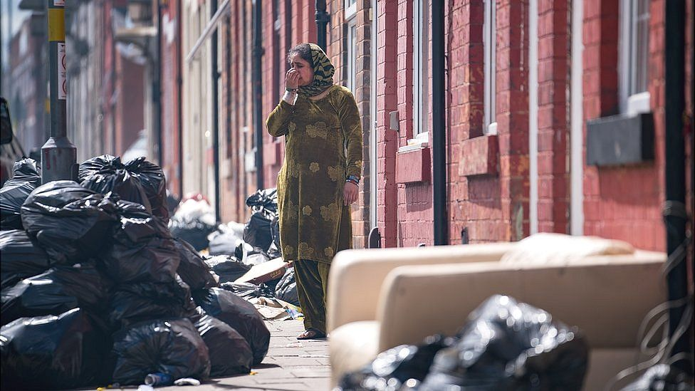 Woman in a street in Alum Rock surrounded by piles of uncollected rubbish bags