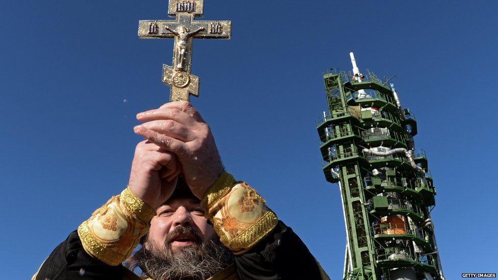 A Russian Orthodox priest conducts a ceremony near a Soyuz spacecraft before launch