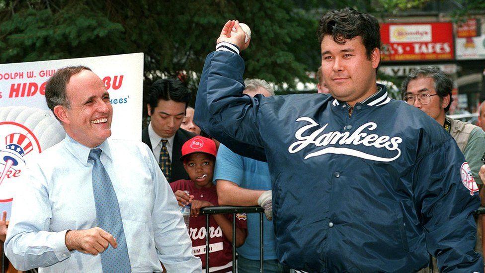 New York Yankees pitcher Hideki Irabu (R) shows his form to New York City Mayor Rudolph Giuliani at a city hall ceremony in New York