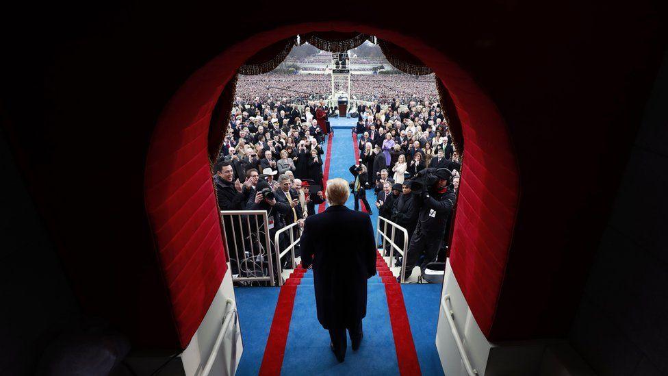 Trump walks through the doorway to the inauguration podium