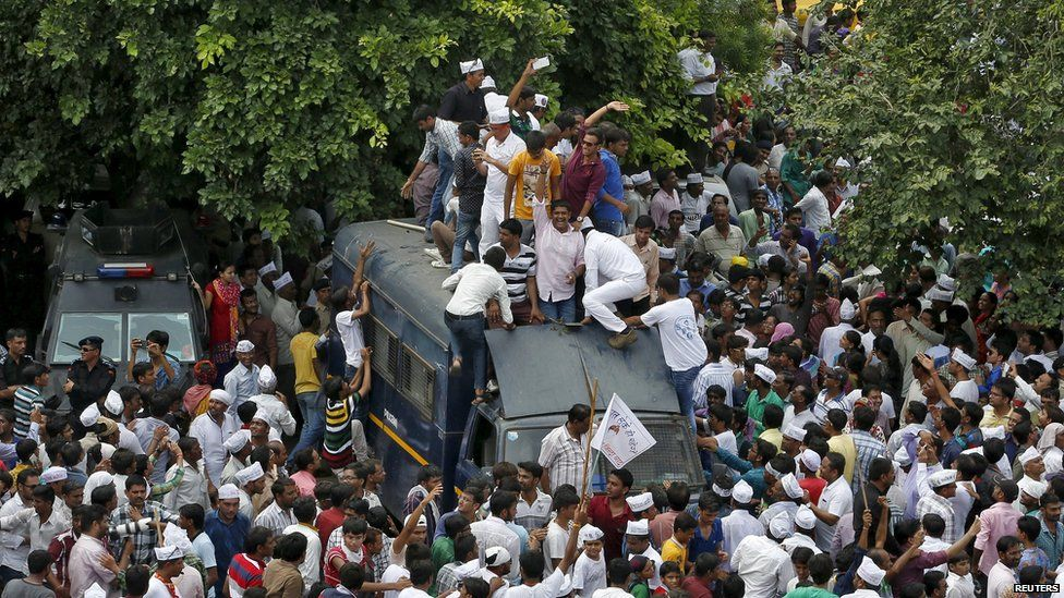 Members of the Patel community climb a police vehicle as they attend a protest rally in Ahmedabad, India, August 25, 2015.