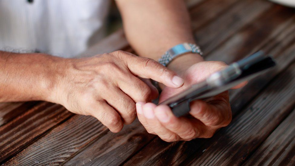 File photo of an elderly Japanese man's hands typing on a smartphone
