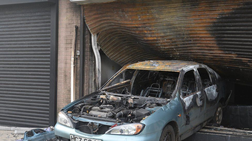 A car reversed through the metal shutter of the hairdressers