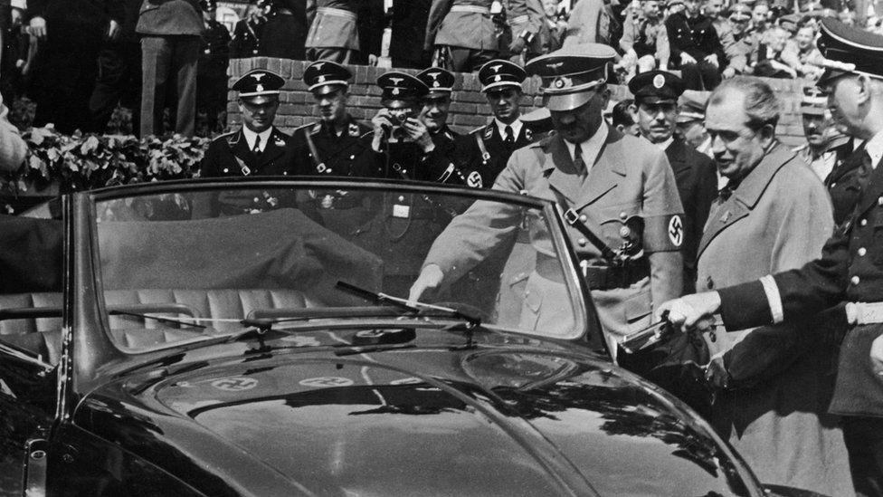Adolf Hitler inspects the new Volkswagen 'people's car' on 27 May 1938. On Hitler's left is the car's designer Dr Ferdinand Porsche