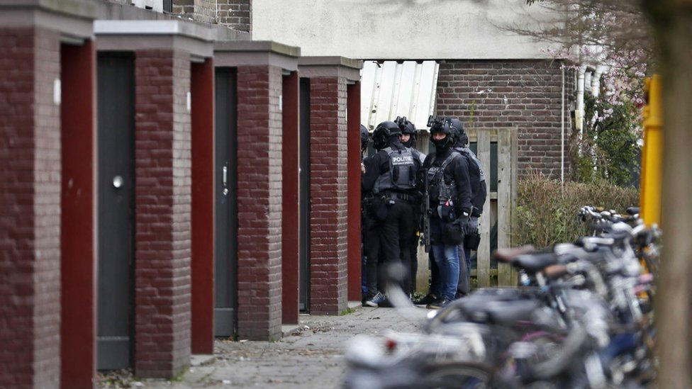 Special task forces of the Dutch police surrounds a building in their search for the attacker