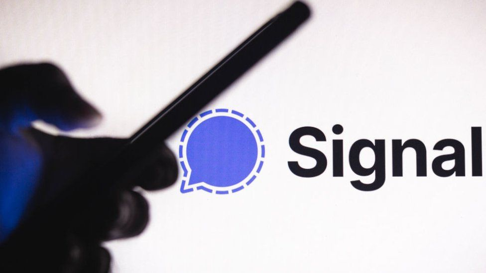 The Signal logo projected behind someone using a phone in silhouette