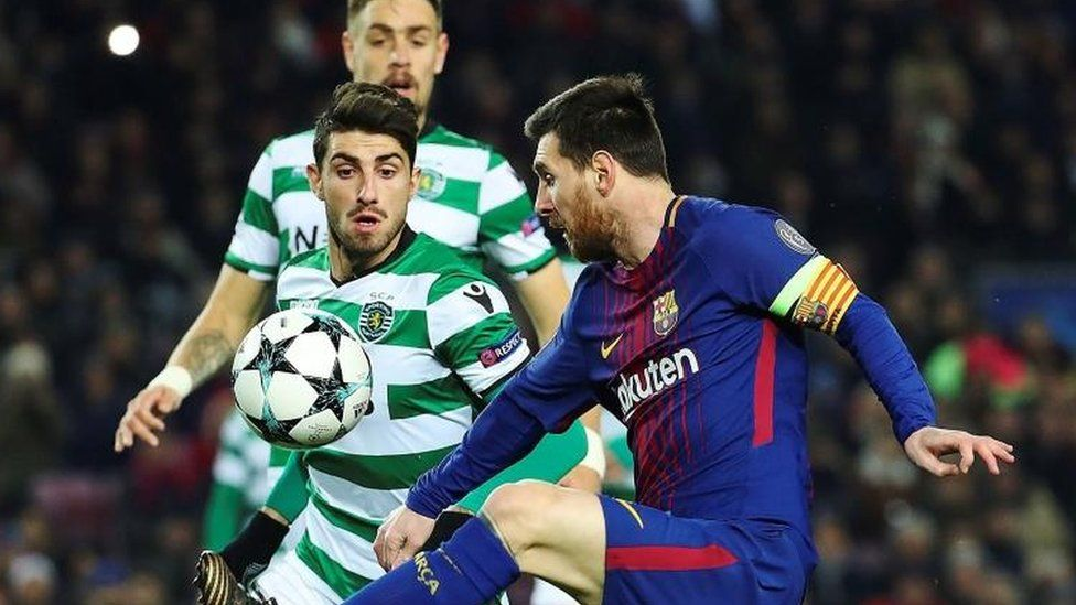 Barcelona's Leo Messi (R) vies for the ball against Sporting Lisbon