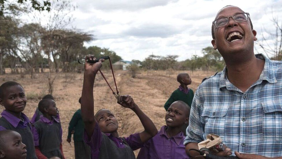 A Kenyan man laughs as children aim a catapult at the sky