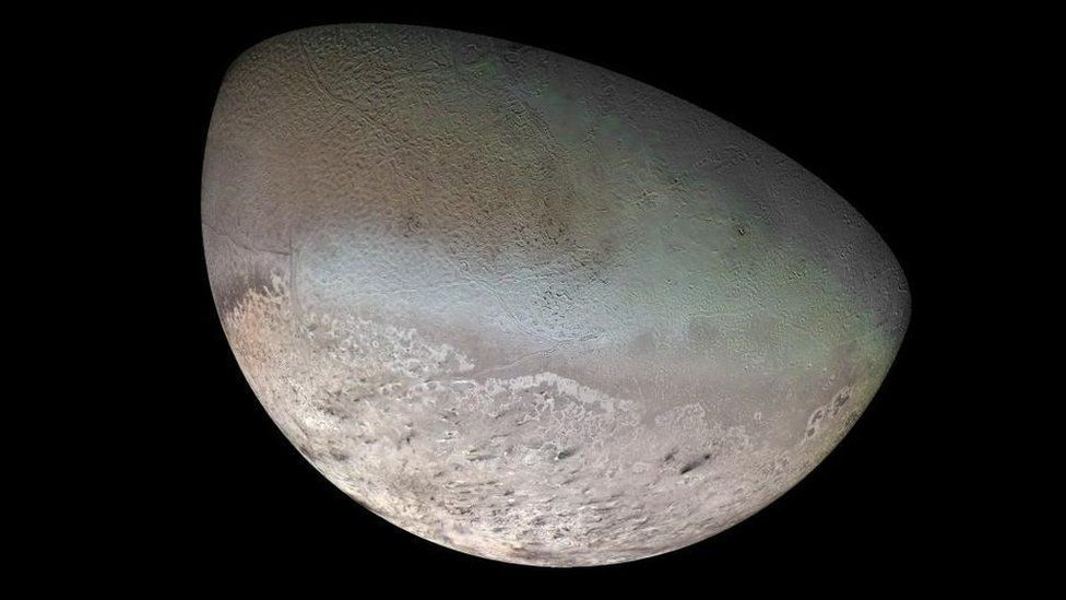 Half the face of Triton, its blue-green surface is mottled like a cantaloupe