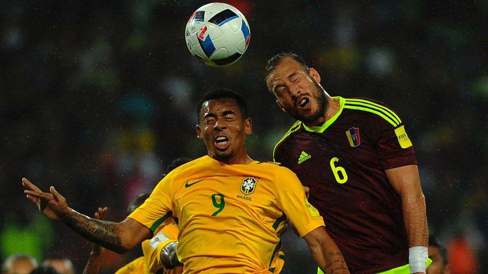 "Brazil's Gabriel Jesus (L) and Venezuela""s defender Jose Manuel Velazquez jump for a header"