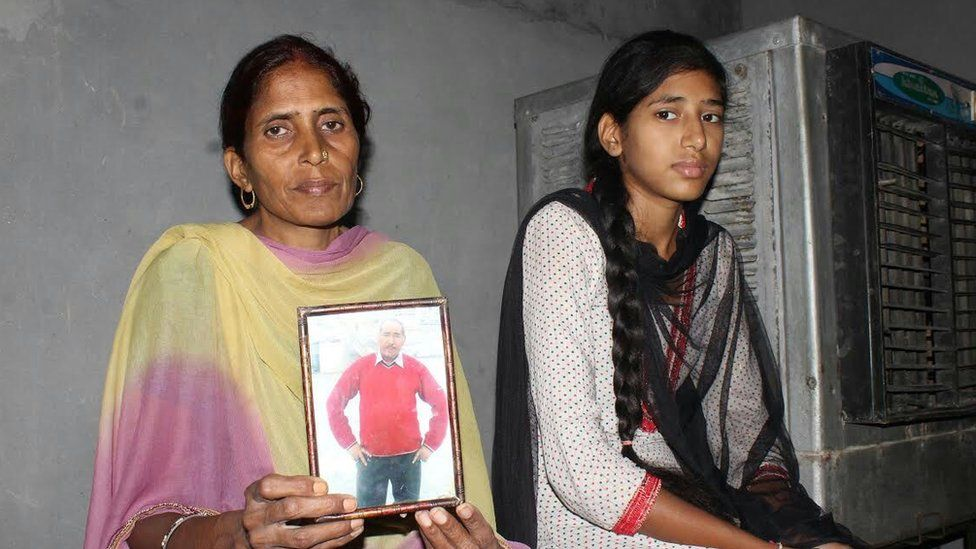 Rajrani Sharma (L) the wife of one of the workers and their daughter, Diksha