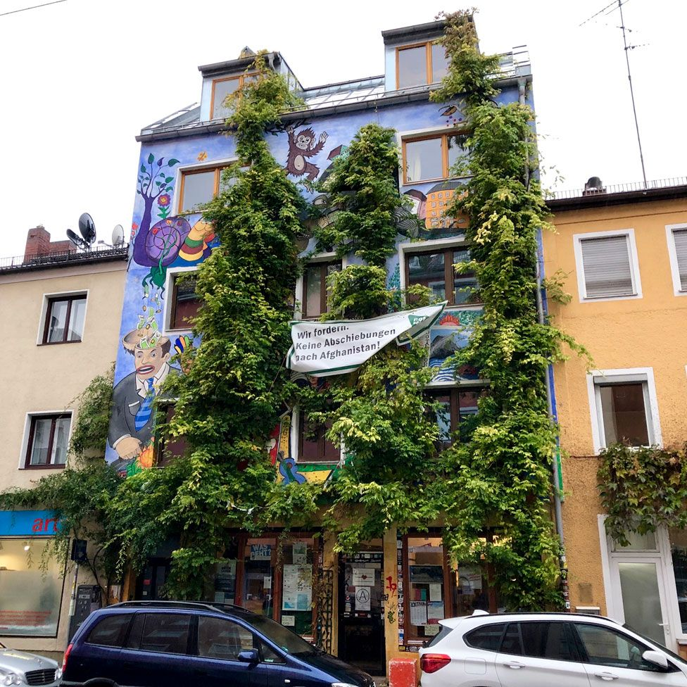 Ligsalz8 is pictured covered in green climbing plants with brightly-painted murals, in stark contrast to the standard terraced buildings on either side