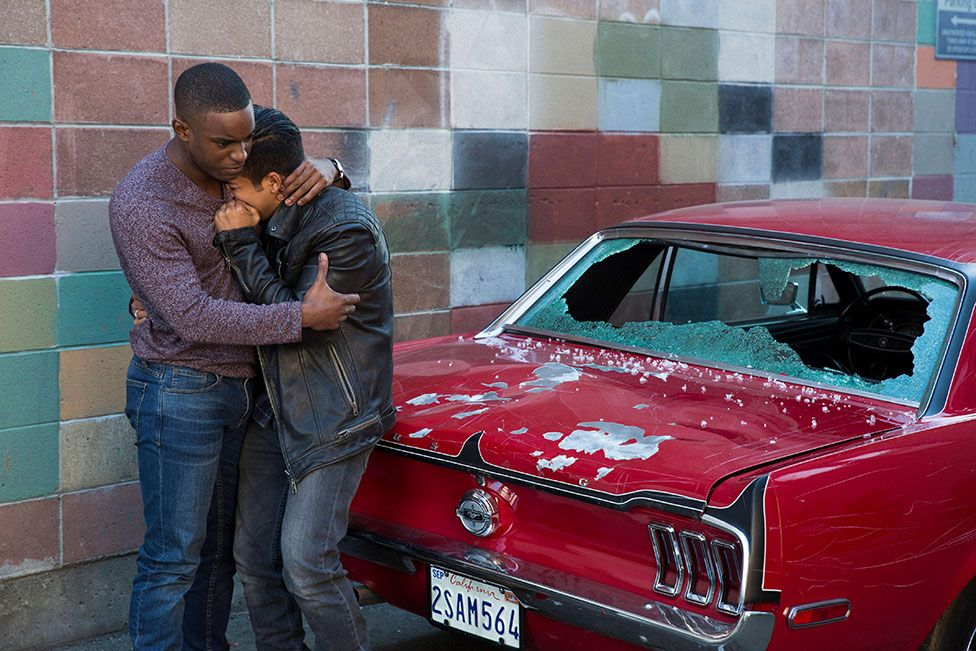 Characters Caleb and Tony hug each other in front of a smashed car