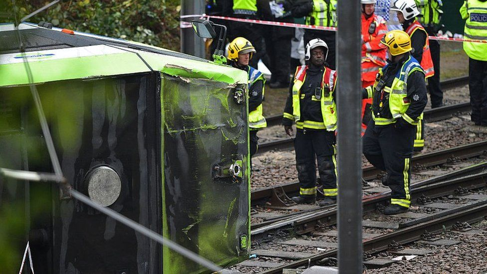 Members of London Fire Brigade look at the overturned tram