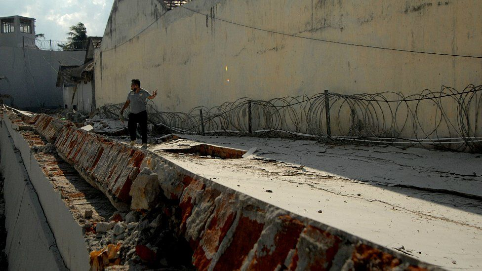 An officer walks at a collapsed prison wall following an earthquake in Palu, Central Sulawesi, Indonesia, October 2, 2018