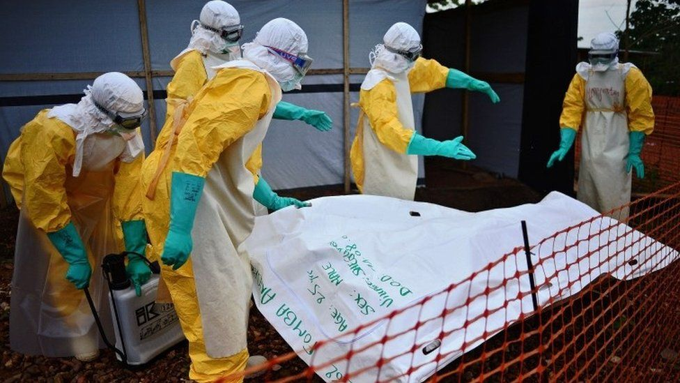Medecins Sans Frontieres (MSF) medical workers disinfect the body bag of an Ebola victim at the Medecins Sans Frontieres (MSF) facility in Kailahun, on August 14, 2014
