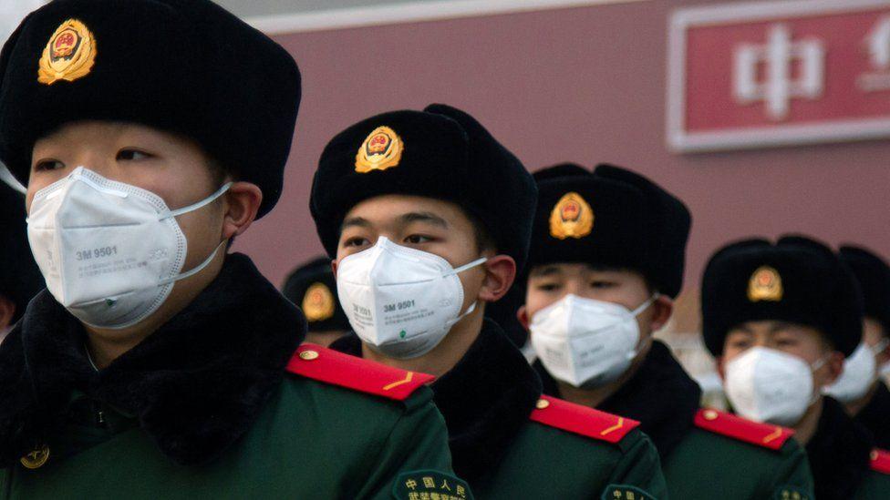 Chinese policemen wearing face masks