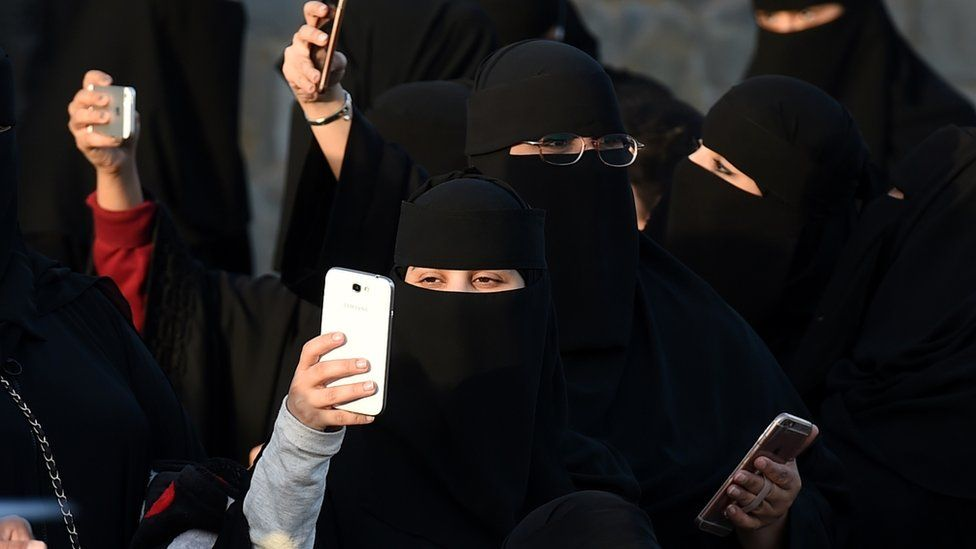 Saudi women use their mobile phones during the Janadriyah festival of Heritage and Culture held in the Saudi village of Al-Thamama, 50 kilometres north of the capital Riyadh