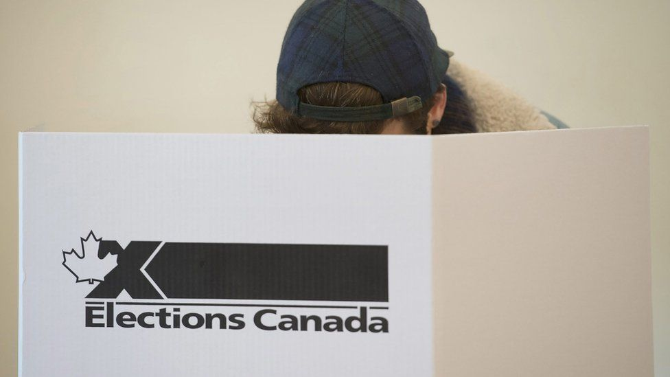 A voter casts a ballot behind an 'Elections Canada' sign.