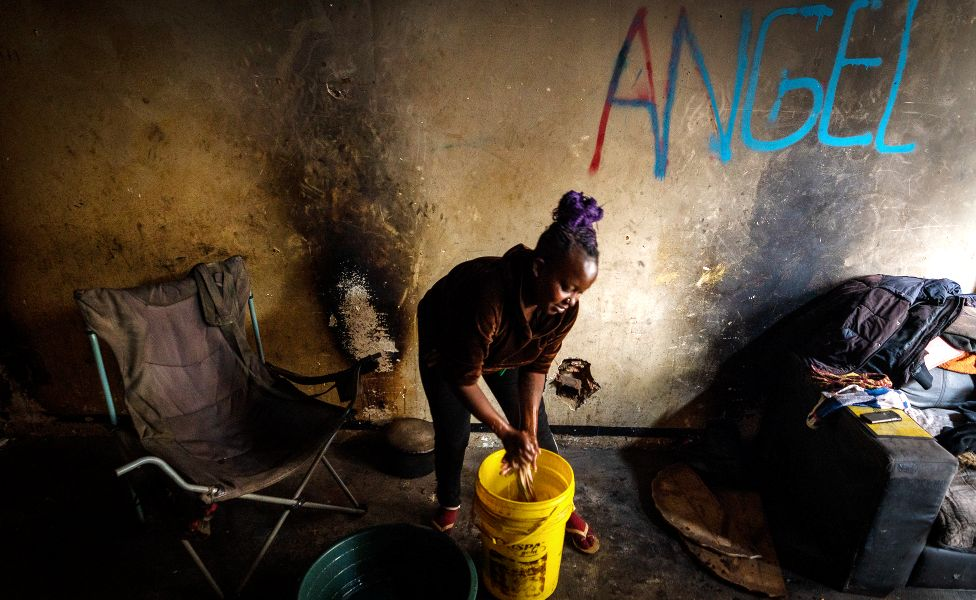 Angela doing her daily chores, washing clothing from a plastic bucket in the derelict San Jose building in Johannesburg, South Africa