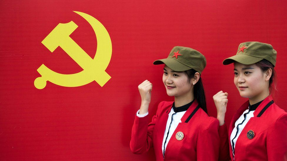 This picture taken on April 21, 2016 in Shaoshan shows Chinese tourists posing in front a flag of the Communist Party of China