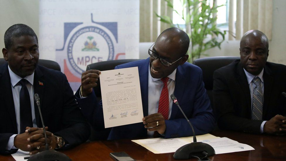 Haiti's Minister of Planning and External Cooperation Aviol Fleurant (centre) shows a statement about the Oxfam case at a news conference in Port-au-Prince on 13 June 2018