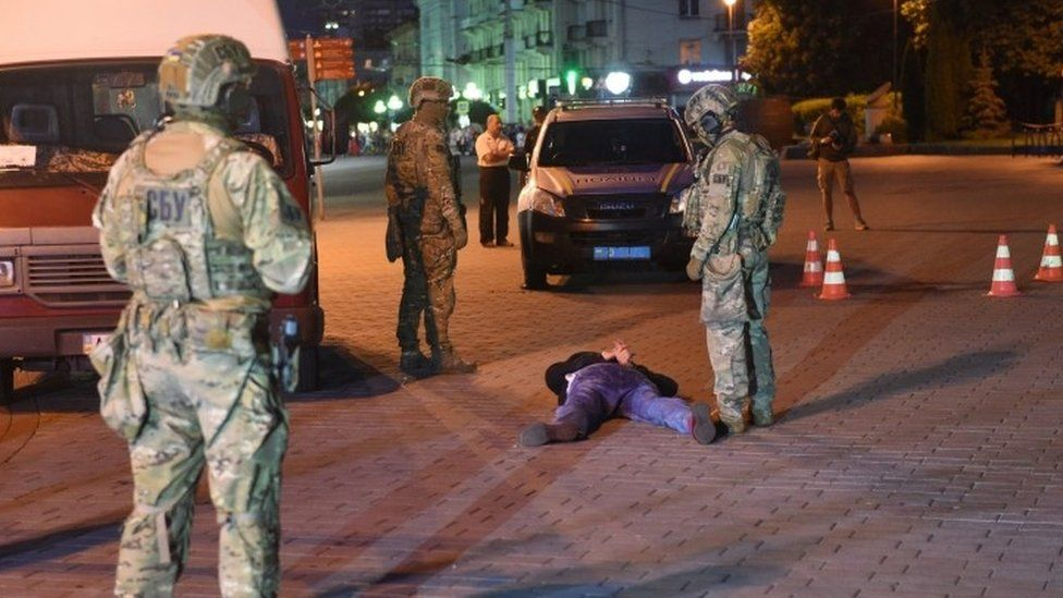 Security forces stand over detained gunman