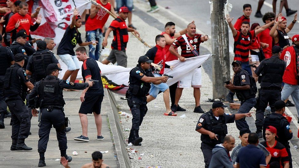 Rio police draw their weapons during clashes with fans at the parade