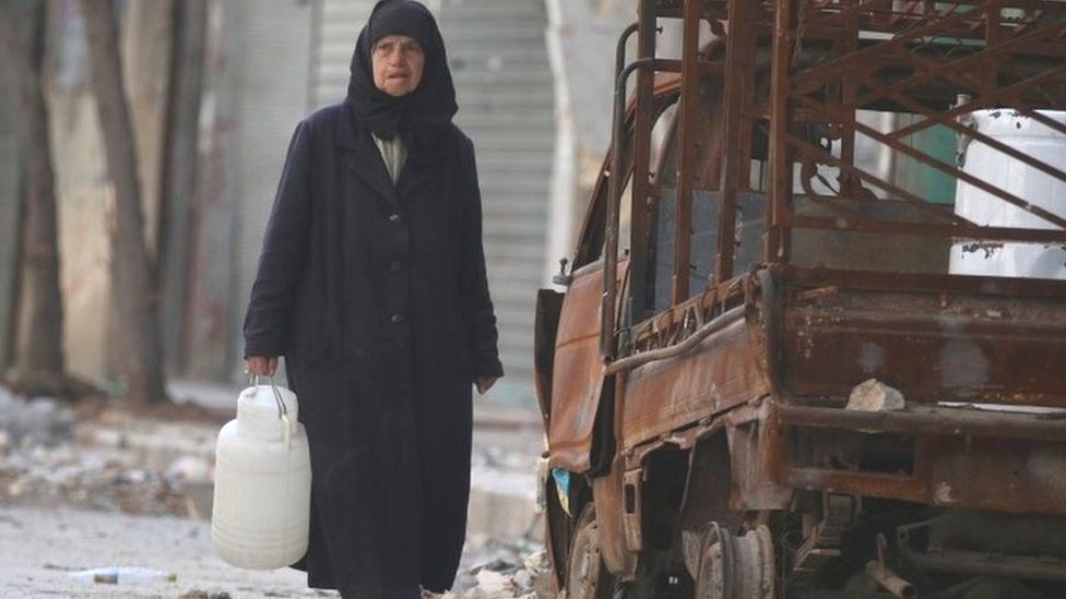 A woman carries a container of water as she walks past a burnt pick-up truck in the rebel held area of Old Aleppo (14 November 2016)