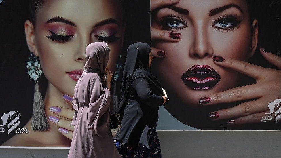 2021 年 8 月 7 日,身穿罩袍的妇女走过贴在喀布尔一家美容院墙上的广告牌