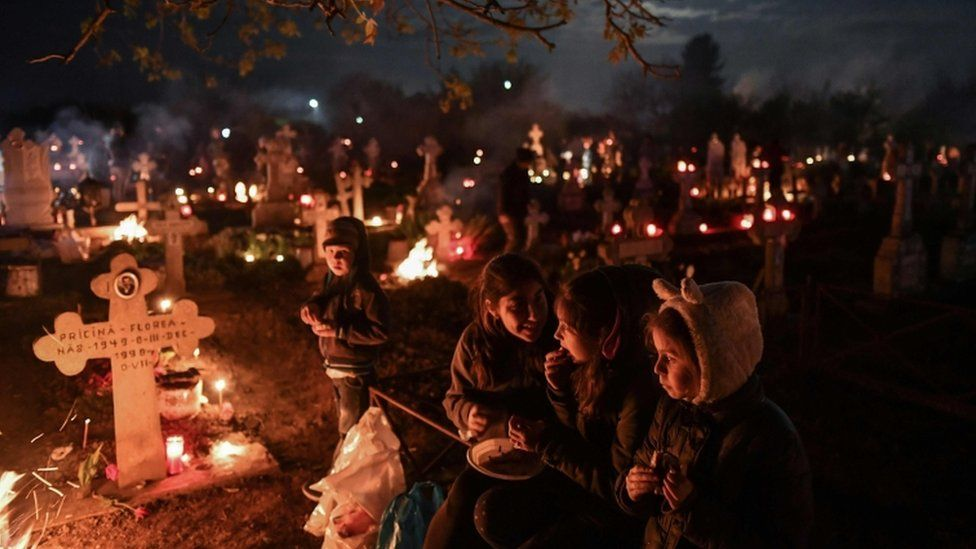 People lit candles and kept vigil at the graves of loved ones during a service in Herasti, Romania.
