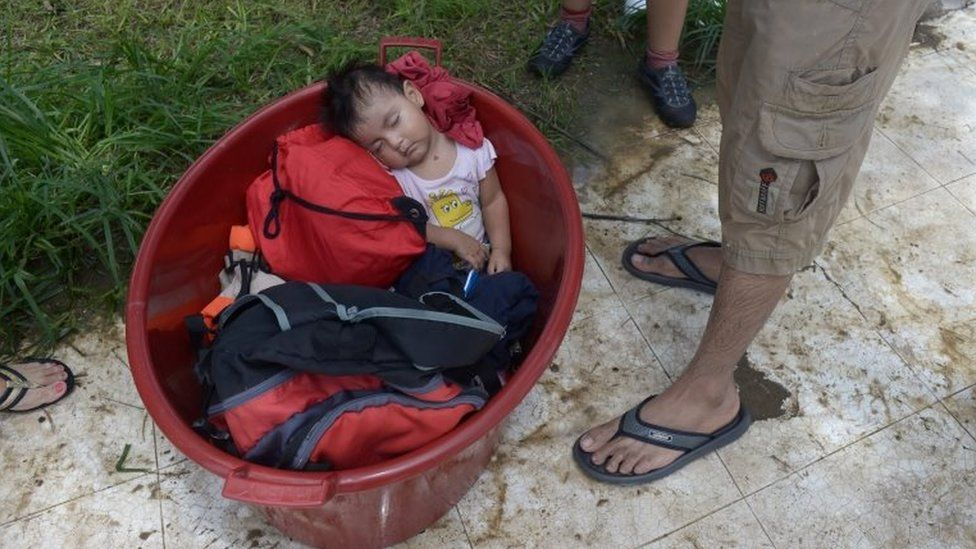 A baby is seen inside a bucket after rivers breached their banks due to torrential rains, causing flooding and widespread destruction in Piura, Peru, March 27, 2017
