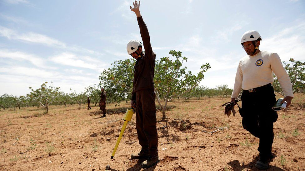 A civil defence member raises his hand after finding a cluster bomb inside an orchard in al-Tmanah town in southern Idlib countryside, Syria (May 21, 2016)