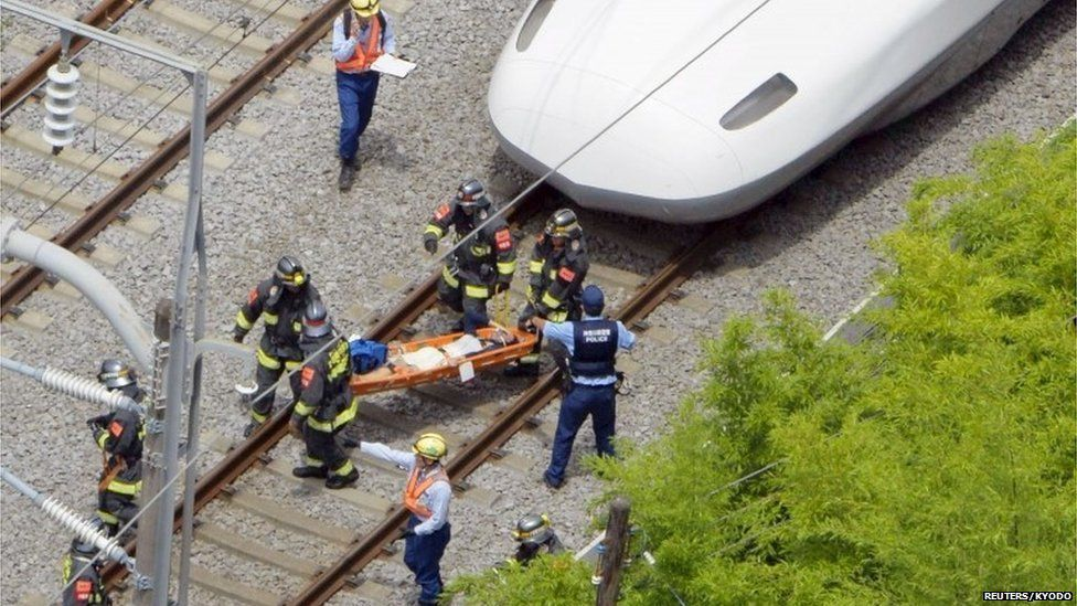 A passenger on the stretcher is carried by rescue workers from a Shinkansen bullet train after it made an emergency stop in Odawara, south of Tokyo, in this aerial view photo taken by Kyodo June 30, 2015.