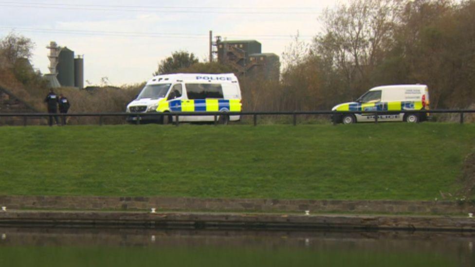 Police vans by river