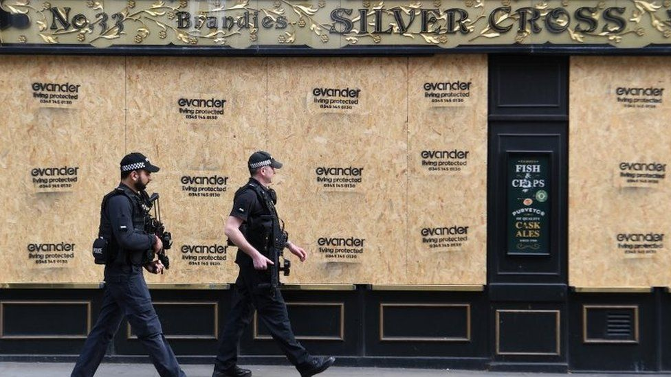 Two police officers walk past a boarded-up pub