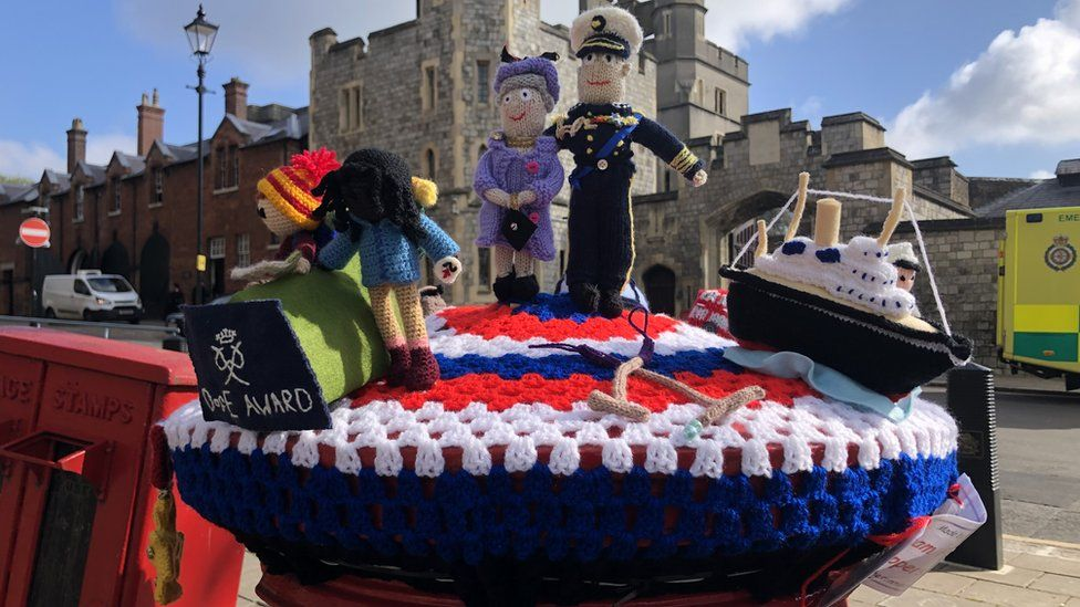 A postbox in Windsor is adorned with crocheted figures of the Queen and Prince Philip, a naval ship and two people doing the Duke of Edinburgh's Award
