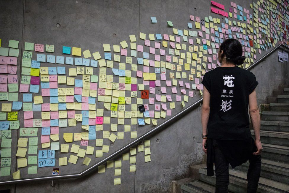 A woman walks past a wall in Hong Kong covered with sticky note messages