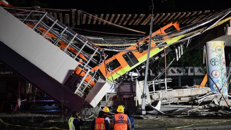 Rescue workers gather at the site of a train accident after an elevated metro line collapsed in Mexico City