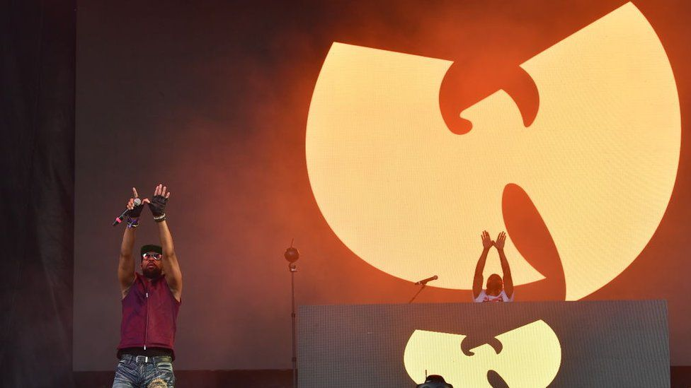 RZA performs in front of a Wu Tang Clan sign