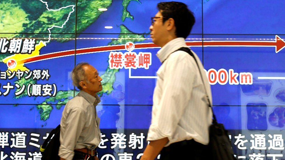 """Passersby walk in front of a TV screen reporting news about North Korea""""s missile launch, in Tokyo, Japan, September 15, 2017."""