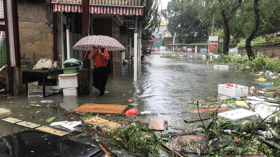 A man wades through floodwaters in the village of Lei Yu Mun during Super Typhoon Mangkhut in Hong Kong on September 16, 2018.
