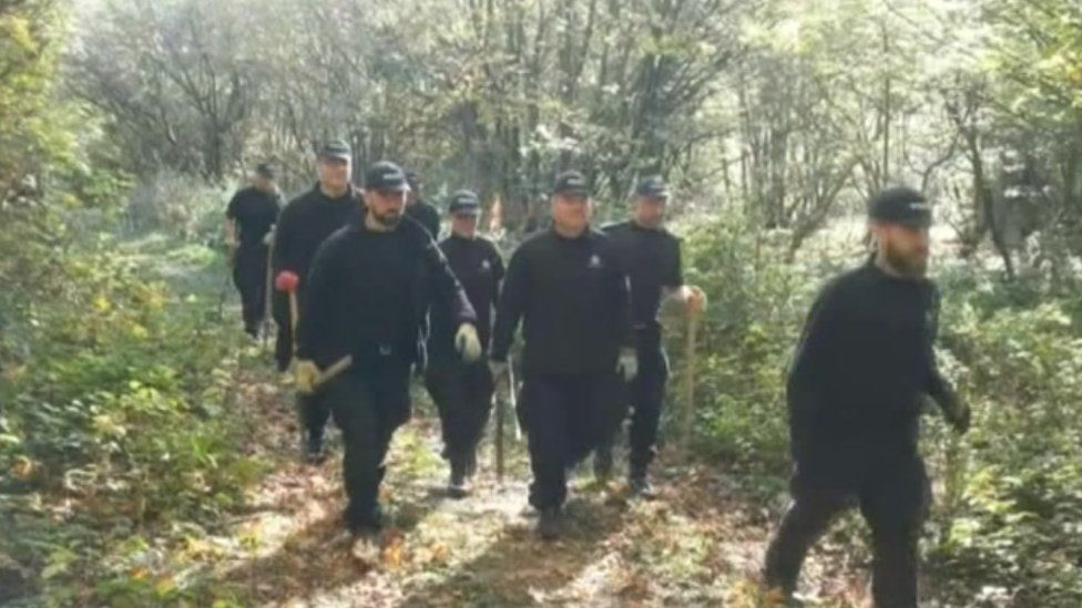 Police officers searching woodland