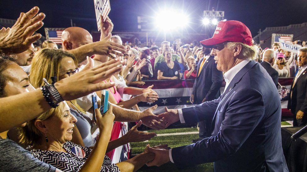 : Republican presidential candidate Donald Trump greets supporters after his rally at Ladd-Peebles Stadium on August 21, 2015 in Mobile, Alabama.